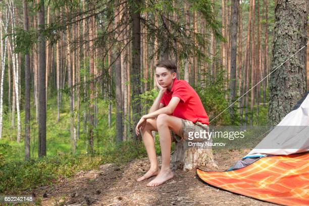 bored teen boy in a summer forest - teen boy barefoot stock photos and pictures