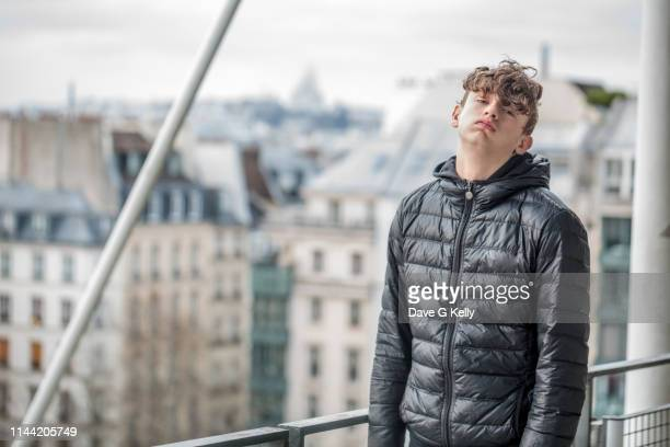 bored teenage boy paris cityscape background - adolescence stock pictures, royalty-free photos & images