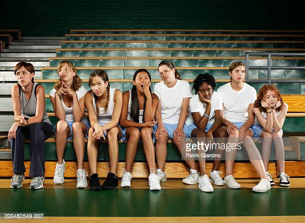 bored teenage girls (12-16) sitting with instructor in gym class - people in a row stock pictures, royalty-free photos & images