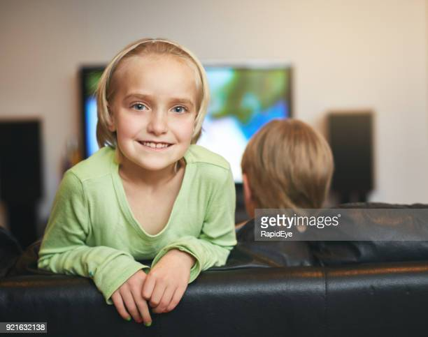 Bored with TV, little girl turns away smiling