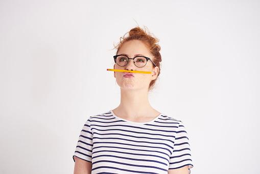 Bored woman having fun with pencil 1023923728