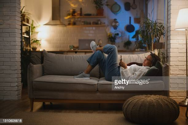 bored woman laying in sofa late at night while using her smartphone - dusk stock pictures, royalty-free photos & images