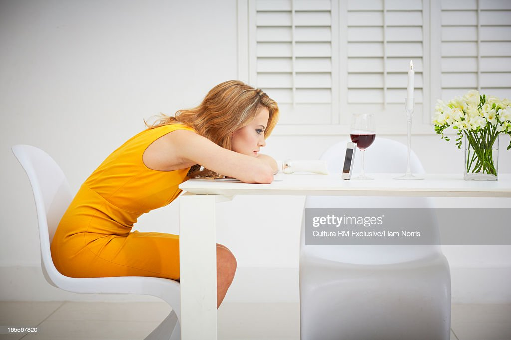 Bored woman using cell phone at table : Stock Photo
