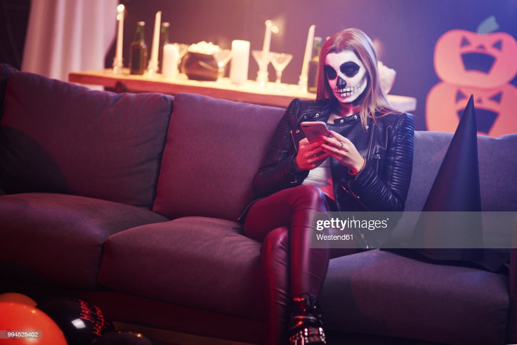 Bored woman using mobile phone at Halloween party : Stock Photo