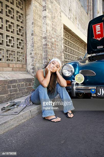 Bored Woman with Dreadlocks Sitting on a Kerb Next to a Broken Down Car