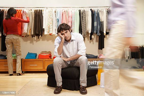 Bored young man in women's clothing store