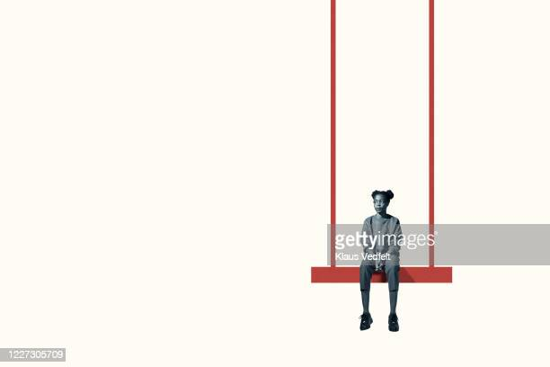 bored young woman sitting on maroon swing - uncertainty stock pictures, royalty-free photos & images