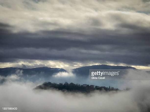 borgo collinare in inverno con nuvole basse e cielo minaccioso - silvia casali stock pictures, royalty-free photos & images