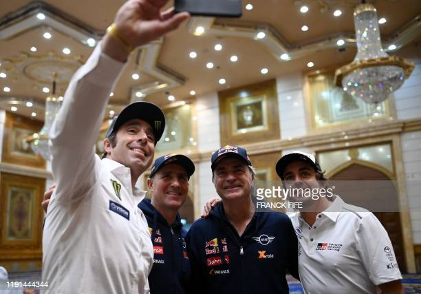 Borgward's driver Nani Roma of Spain takes selfie with Mini's driver Stephane Peterhansel Mini's Spanish drivers Carlos Sainz of Spain and Toyota's...