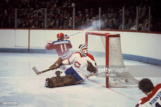 Boris Alexandrov of the Soviet Union shoots the puck past Ken Dryden of the Montreal Canadiens during a game at the Montreal Forum on December 31...