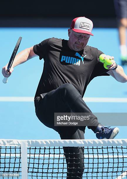 Boris Becker coach of Novak Djokovic of Serbia hops over the net during a practice session ahead of the 2016 Australian Open at Melbourne Park on...