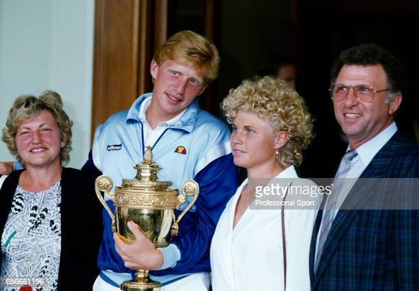 Boris Becker of West Germany with the trophy surrounded by his family after defeating Ivan Lendl of Czechoslovakia on Centre Court during the men's...