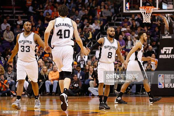 Boris Diaw and Patty Mills of the San Antonio Spurs highfives Boban Marjanovic during the NBA game against the Phoenix Suns at Talking Stick Resort...
