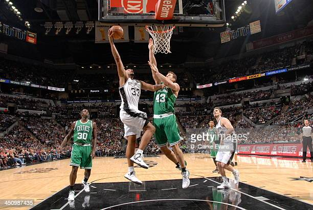 Boris Diaw of the San Antonio Spurs dunks against Kris Humphries of the Boston Celtics at the ATT Center on November 20 2013 in San Antonio Texas...
