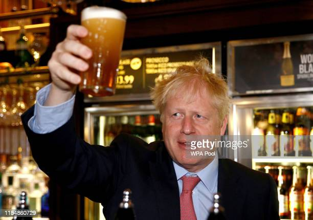 Boris Johnson, a leadership candidate for Britain's Conservative Party holds a pint of beer as he meets with JD Wetherspoon chairman, Tim Martin at...