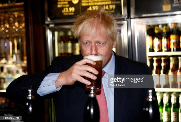 Boris Johnson a leadership candidate for Britain's Conservative Party tastes a pint of beer as he meets with JD Wetherspoon chairman Tim Martin at...
