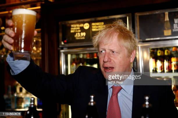 Boris Johnson a leadership candidate for Britain's Conservative Party holds a pint of beer as he meets with JD Wetherspoon chairman Tim Martin at...
