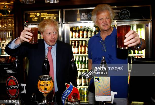 Boris Johnson a leadership candidate for Britain's Conservative Party pulls a pint as he meets with JD Wetherspoon chairman Tim Martin at...