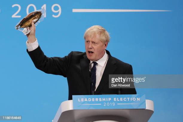 Boris Johnson holds a kipper to help illustrate a point as he talks at the final hustings of the Conservative leadership campaign at ExCeL London on...