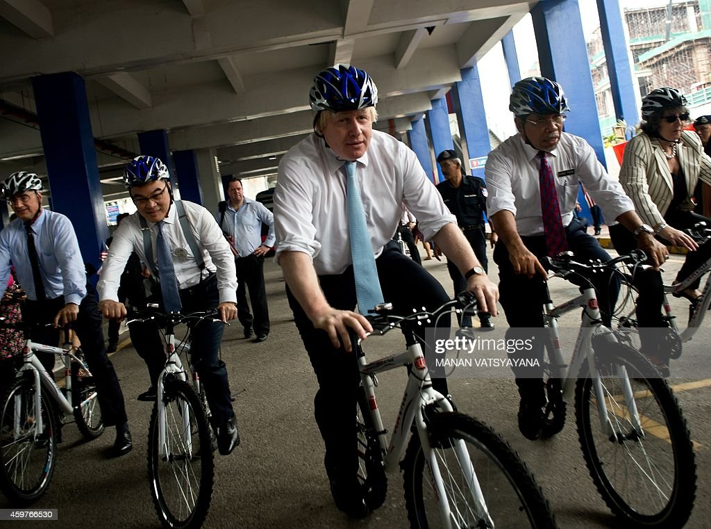 Boris Johnson, Mayor of London(C) rides a bicycyle on a city-tour in Kuala Lumpur on December 1, 2014. Johnson is in Malaysia as part of his six-day trade mission to the Far East which include Jakarta and Singapore.