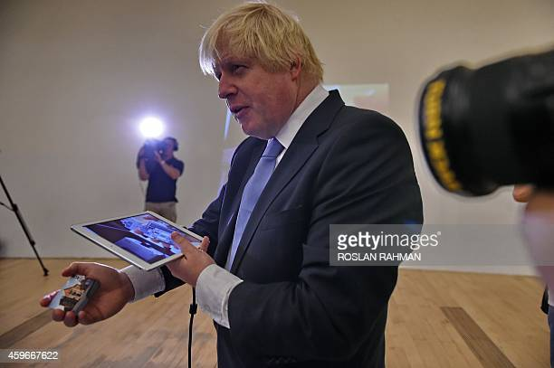 Boris Johnson Mayor of London uses a virtual supermarket app on a tablet at the ArtScience museum where he will deliver his speech during FinTech...