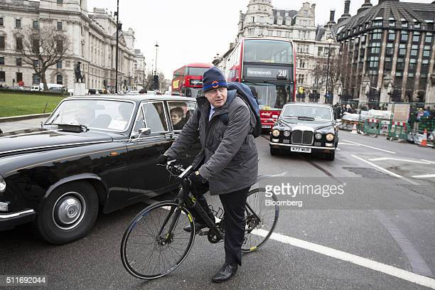 Boris Johnson mayor of London waits in traffic on his bicycle as he departs the Houses of Parliament in London UK on Monday Feb 22 2016 The pound...