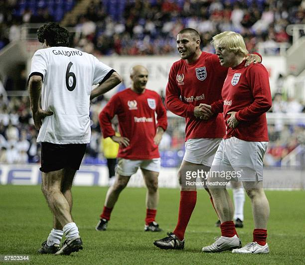 Boris Johnson MP of England is congratulated by Ben Cohen after fouling Maurizio Gaudino of Germany during the Legends match between England and...
