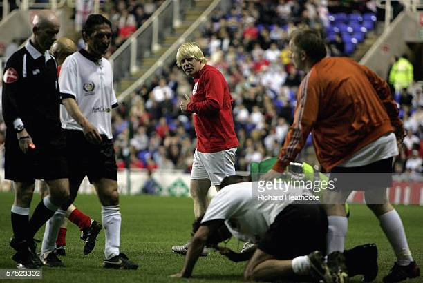Boris Johnson MP of England looks on after fouling Maurizio Gaudino of Germany during the Legends match between England and Germany at The Madejski...