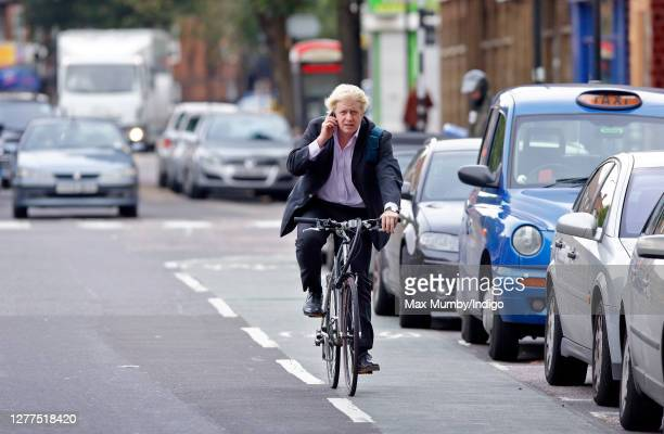 Boris Johnson seen riding his bike one handed whilst using his mobile phone as he cycles to work on October 5, 2006 in London, England.