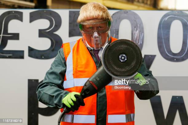 Boris Johnson the former mayor of London holds an angle grinder at the Reid Steel factory during the second day of a nationwide bus tour to campaign...