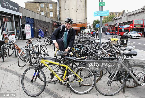 Boris Johnson the Mayor of London puts on his bicycle clips before cycling from Highbury and Islington Station on August 17 2011 in London England Mr...