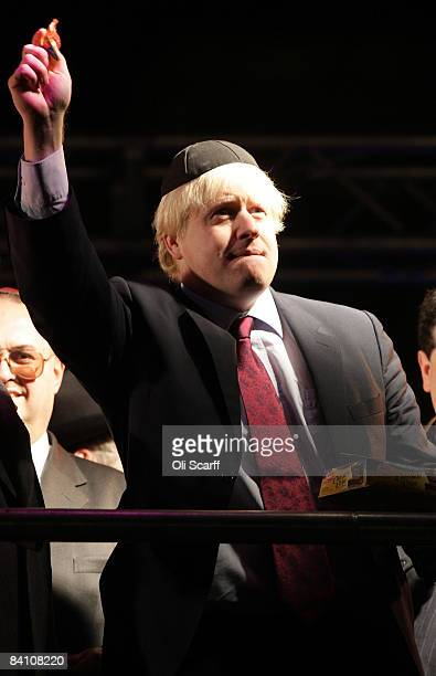 Boris Johnson the Mayor of London throws Chanukah Gelt chocolate coins into the crowd after he helped to light a sacred Menorah in Trafalgar Square...