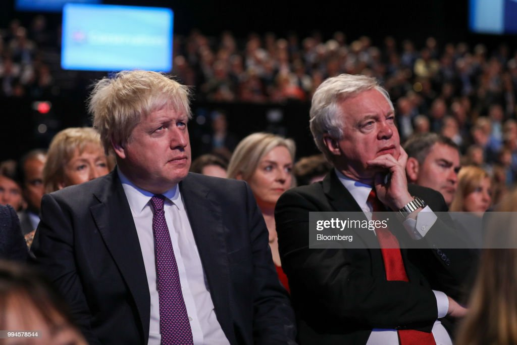 Boris Johnson, U.K. foreign secretary, left, and David Davis, U.K. exiting the European Union secretary, attend the speech by Theresa May, U.K. prime minister and leader of the Conservative Party, at the party's annual conference in Manchester, U.K., on Wednesday, Oct. 4, 2017. Johnson resigned from the U.K. government, tipping Prime Minister Theresa May deeper into crisis and increasing the chances shell face a leadership challenge over her Brexit policy. Hours earlier Brexit Secretary David Davis and his deputy resigned over her plans to keep close ties to the European Union after the divorce. The man who is going to inherit one of the toughest jobs in the U.K. -- negotiating Brexit -- is a 44-year-old former Foreign Office lawyer who entered Parliament in 2010: Dominic Raab. Our editors select the best archive images of Raab, Davis and Johnson. Photographer: Chris Ratcliffe/Bloomberg via Getty Images