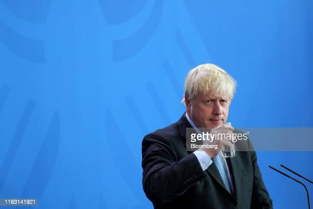 Boris Johnson UK prime minister holds a glass of water during a news conference with Angela Merkel Germany's chancellor not pictured at the...