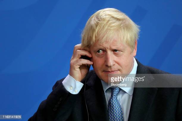 Boris Johnson UK prime minister holds his earpiece during a news conference with Angela Merkel Germany's chancellor not pictured at the Chancellery...