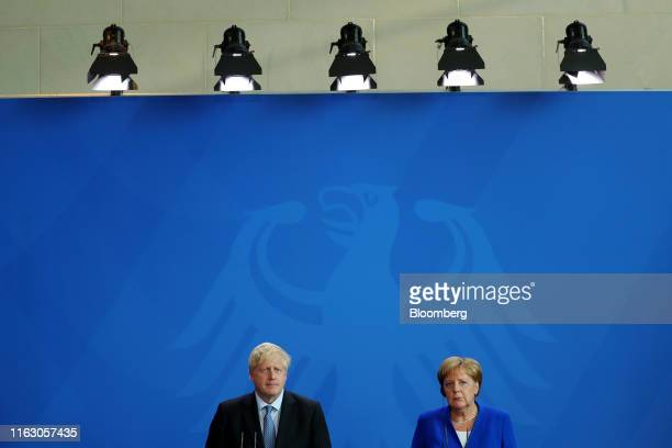 Boris Johnson UK prime minister left and Angela Merkel Germany's chancellor listen during a news conference at the Chancellery in Berlin Germany on...