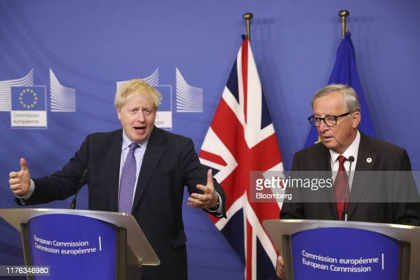 Boris Johnson UK prime minister left gestures during a news conference with JeanClaude Juncker president of the European Commission after negotiators...