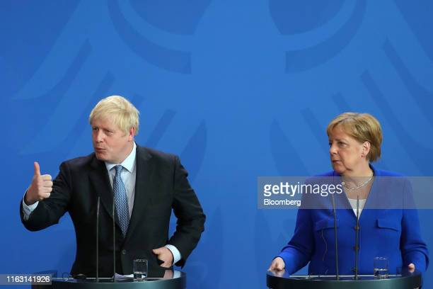 Boris Johnson UK prime minister left gestures while speaking beside Angela Merkel Germany's chancellor during a news conference at the Chancellery in...