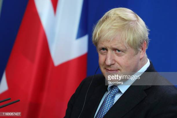 Boris Johnson UK prime minister listens beside Angela Merkel Germany's chancellor not pictured during a news conference at the Chancellery in Berlin...