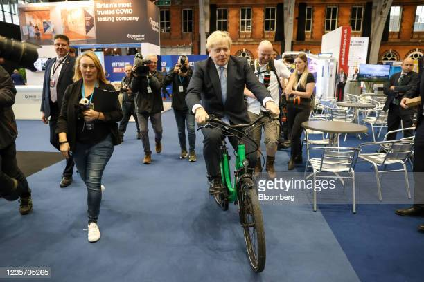 Boris Johnson, U.K. Prime minister, rides a bicycle on day three of the annual Conservative Party conference in Manchester, U.K., on Tuesday, Oct. 5,...