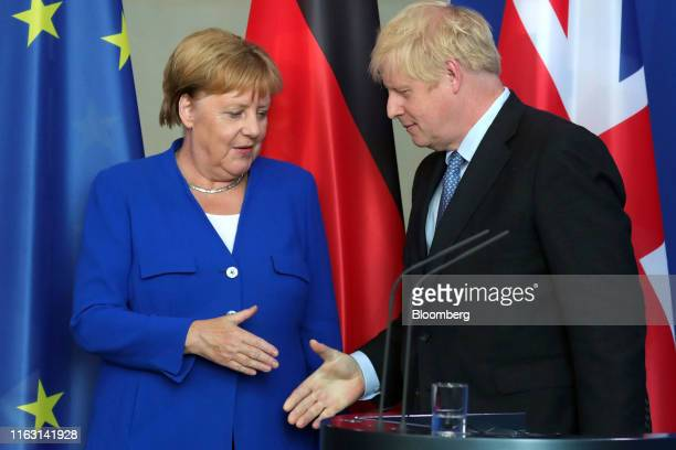 Boris Johnson UK prime minister right and Angela Merkel Germany's chancellor shake hands following a news conference at the Chancellery in Berlin...