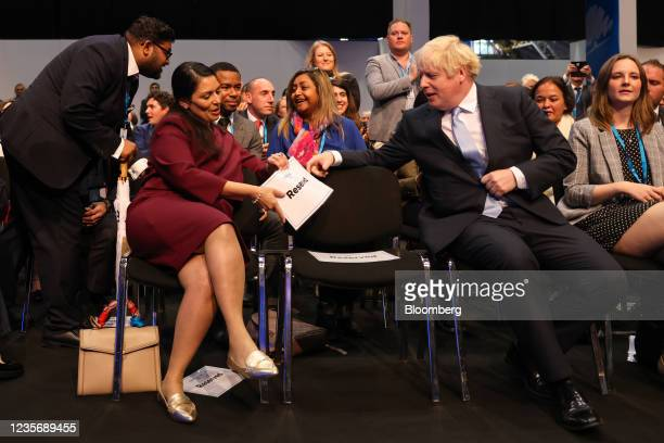"""Boris Johnson, U.K. Prime minister, right, hands a sign reading """"reserved"""" to Priti Patel, U.K. Home secretary, on day two of the annual Conservative..."""