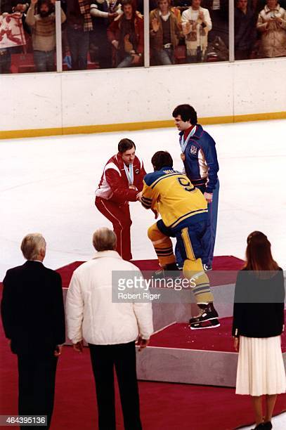 Boris Mikhailov of the Soviet Union shakes hands with Mats Waltin of Sweden as Mike Eruzione of the United States looks on during the medal ceremony...
