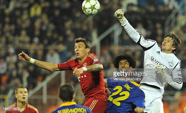 Borisov's goalkeeper Andrei Gorbunov and Marko Simic fight for the ball against Bayern Munich's Dante and Mario Mandzukic during on their Champions...