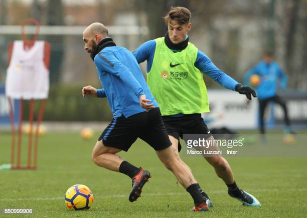 Borja Valero competes with Andrea Pinamonti during the FC Internazionale training session at the club's training ground Suning Training Center in...