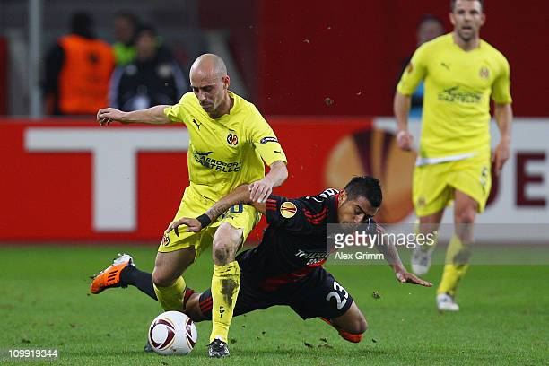 Borja Valero of Villarreal is challenged by Arturo Vidal of Leverkusen during the UEFA Europa League round of 16 first leg match between Bayer...