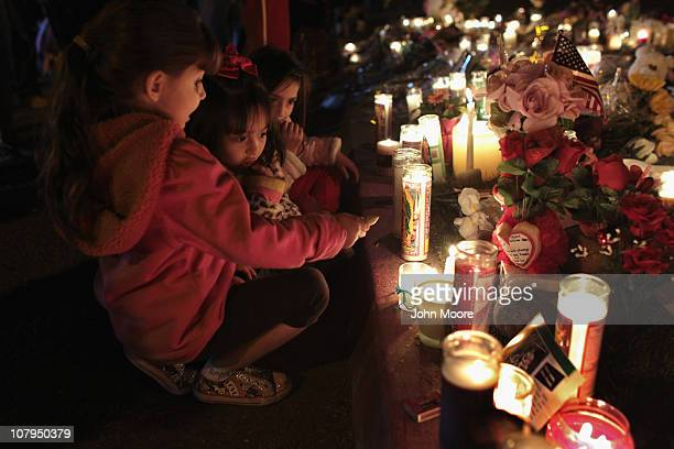 S born children of Mexican immigrants gaze at a makeshift shrine at the University Medical Center for those killed and wounded during an attack on US...