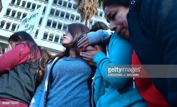 US born daughters of undocumented Romulo AveliaGonzalez who was arrested by ICE agents last week and supporters attend a rally in downtown Los...