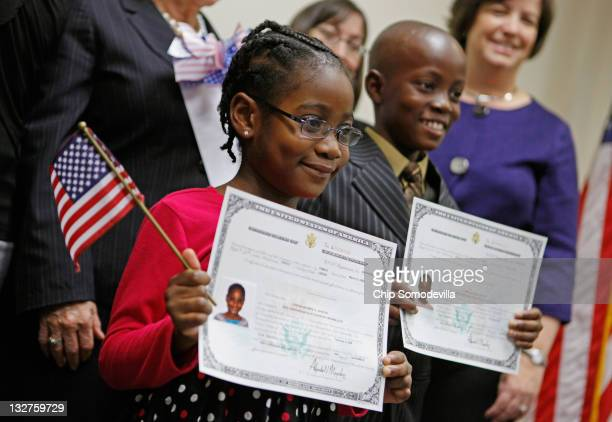 Born in Liberia Cynthia Newton and her brother James Newton pose for photographs with their citizenship certificates during the children's...