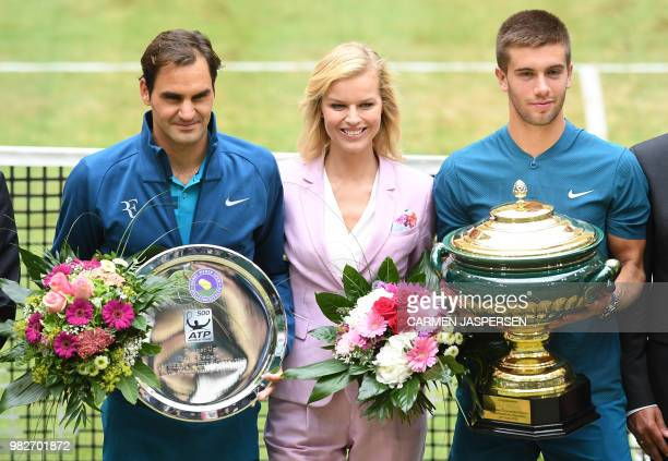 Borna Coric from Croatia poses with his trophy next to Czech model Eva Herzigova after defeating Roger Federer of Switzerland in their final match at...